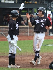 Rice's Reese Trahey (2) high fives teammate Gabe Sotres after scoring what proved to be the game-winning run in the sixth inning.