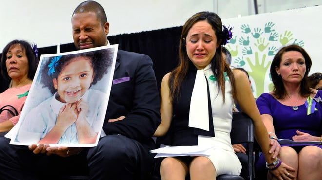 Jimmy Greene and Nelba Marquez-Greene, parents of Sandy Hook Elementary School shooting victim Ana Marquez-Greene, shown in the large photograph, and Nicole Hockley, right, mother of victim Dylan Hockley, react during a news conference at Edmond Town Hall in Newtown, Conn., in January.
