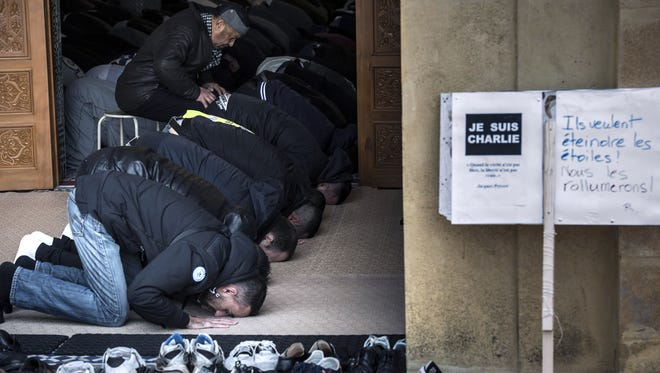 """Muslims pray in the Grande Mosque of Saint-Etienne on Friday in Paris, next to a sign reading """"I am Charlie,"""" for Charlie Hebdo."""