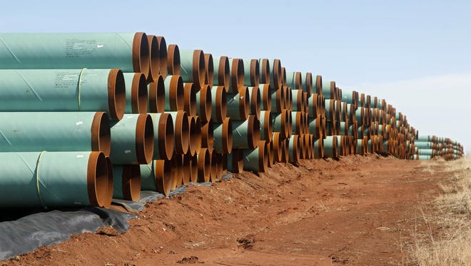 In this Feb. 1, 2012, file photo, miles of pipe for the stalled Canada-to-Texas Keystone XL pipeline are stacked in a field near Ripley, Okla.