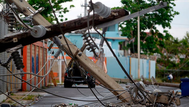 Power line poles downed by the passing of Hurricane Maria lie on a street in San Juan, Puerto Rico on Nov. 7, 2017.