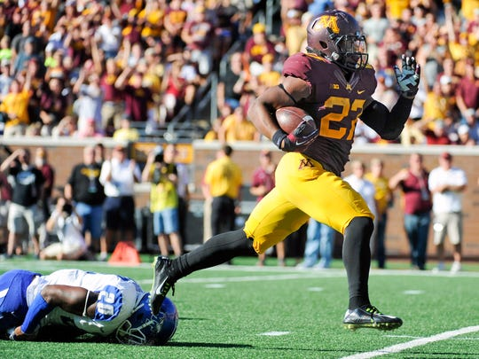 Minnesota running back David Cobb (27) runs past MTSU safety Kevin Byard (20) for a 48-yard touchdown during the second half on Saturday, Sept. 6, 2014, in Minneapolis.