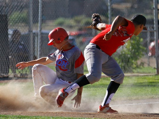 4-Corners' Andrew Caliendo slides past Naa'taanii's Carlos Dominguez at third base on Tuesday at the Farmington Sports Complex.