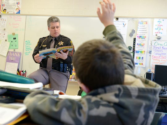 St. Clair County Undersheriff Tom Buckley reads a story as Hunter Megie, 9, raises his hand Monday during a male reading day celebrating March is Reading Month at Kimball Elementary.