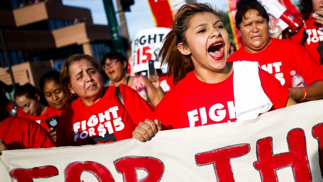 Carolina Maldonado, center, marches with activists in Phoenix in support of an increased minimum wage in April.