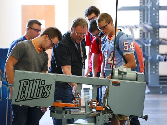 Manufacturing instructor Jerry Torresdal, center, speaks with Spencer Christian, right, a junior at South Salem, and Joe Glascock, a senior at North Salem, about an Ellis bandsaw at the recently opened Career Technical Education Center, Thursday, September 10, 2015, in Salem, Ore.