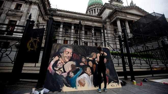 Artist Angeles Crovetto works on a mural of late Argentina's President Nestor Kirchner, top left in the painting, outside the National Congress in Buenos Aires, Argentina,