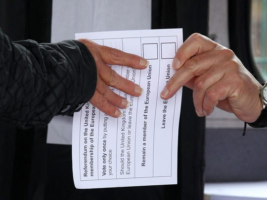 A volunteer hands an unmarked ballot paper to a voter