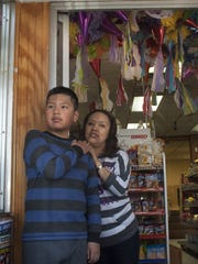 Silvia Ramos and her son Alexander Ramos stand by the door of Alex's Bakery in Woodlynne, where a family member was slain in a 2009 holdup.