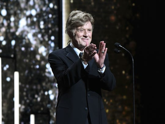 Actor and director Robert Redford applauds on stage