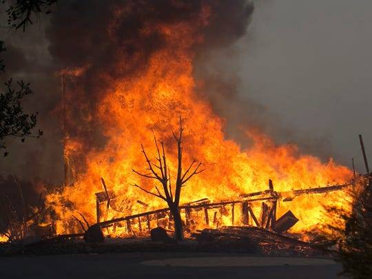 Flames from a wildfire consume a home  east of Napa,