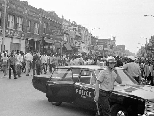 A police car blocks off an area of 12th Street in Detroit where racial violence erupted, July 23, 1967. Police were met by a hail of bottles, bricks and fruit when they tried to clear about 400 people from the streets and sidewalks Sunday afternoon. (AP Photo/Alvan Quinn)