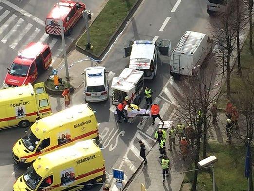 Rescue teams evacuate wounded people outside the Maalbeek