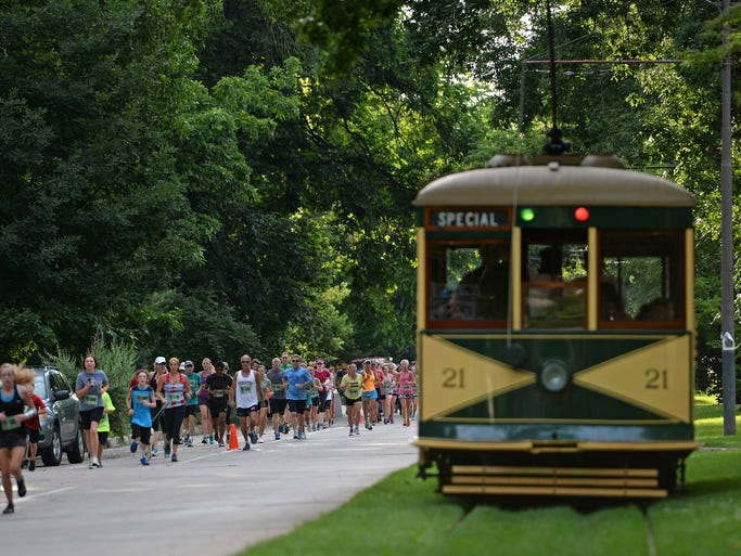 "5K and 10K runners ""race against the trolley"" on Mountain Avenue next to the Fort Collins Municipal Railway Trolley during the Human Race 5K, 10K and half marathon in Fort Collins Saturday, July 26, 2014."