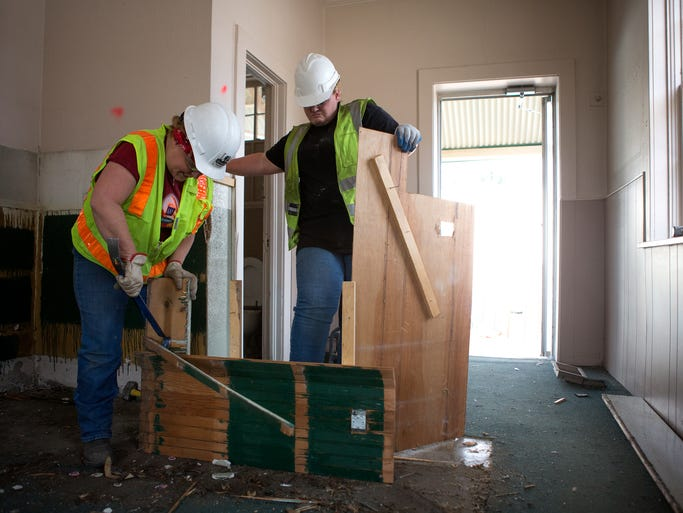 April Heitschmidt, left, and Melody Richards take down wood paneling at the future non-profit FoCo Cafe building on Maple Street in Fort Collins Thursday, August 14, 2014. The women are part of the National Center for Craftsmanship program which provides training to adults and youth in deconstruction, construction and recycling techniques.