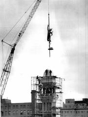 1974: Statue of Mercury is hoisted atop the Lawyers' Co-Op building