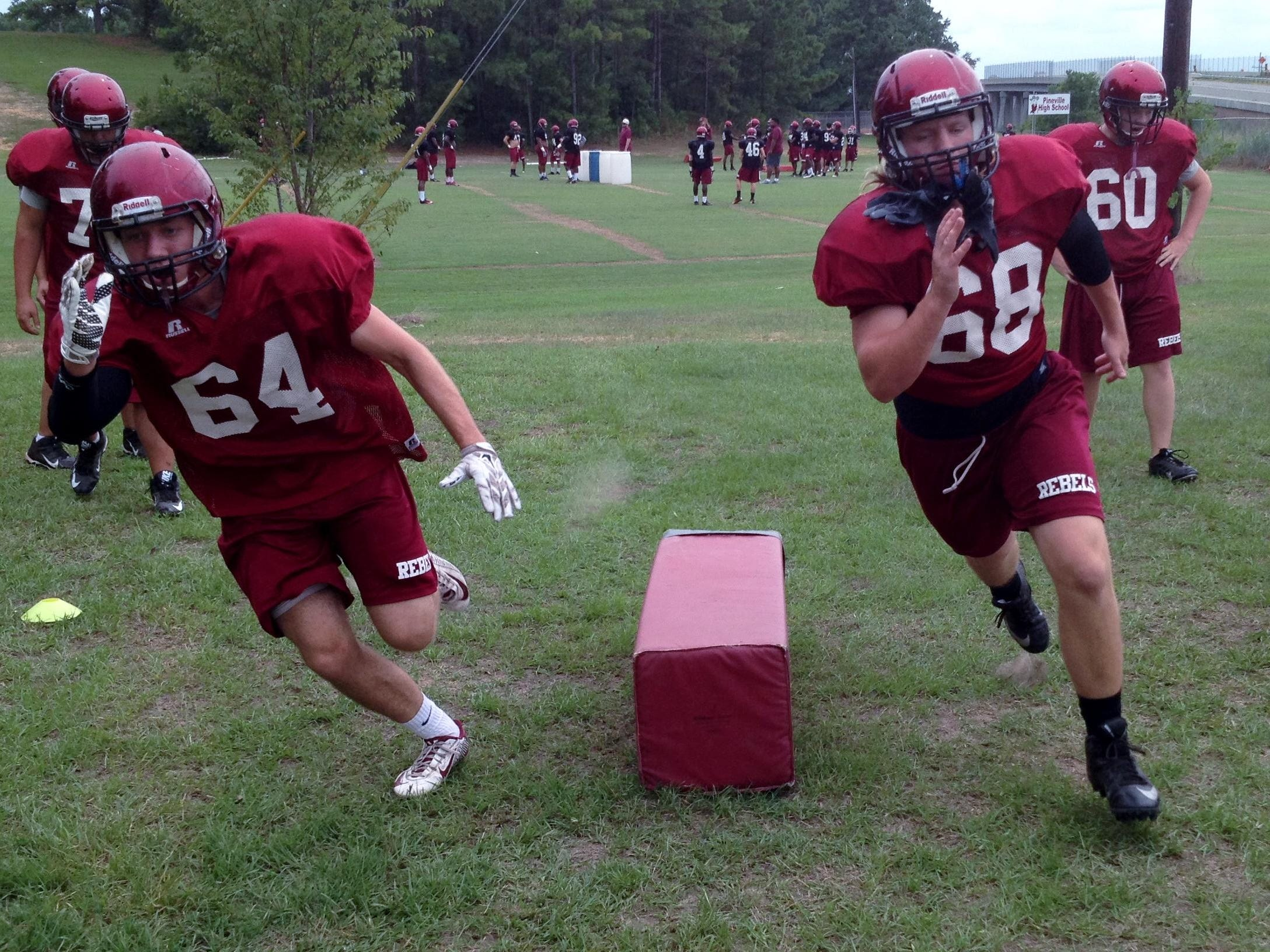 Pineville senior right tackle Harrison Nugent (64) and right guard Dakota Cross (68) run through a drill during practice Tuesday. The undersized Nugent is one of the top academic and most involved students at Pineville High School.