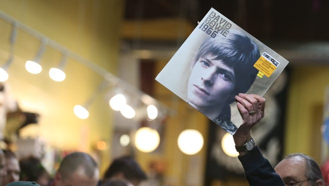 Archive: Record Archive staffers hold up albums, including David Bowie 1966, for shoppers to better locate.
