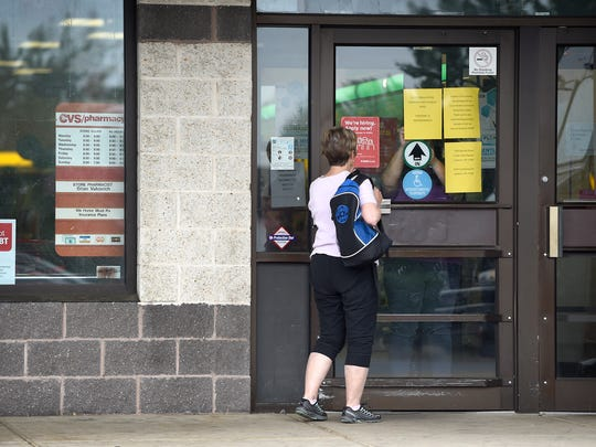 Lebanon police have arrested two after a break in at CVS pharmacy, 833 Bowman St., Monday, June 5, 2017. A customer watches as an employee post a sign in the window Monday morning.
