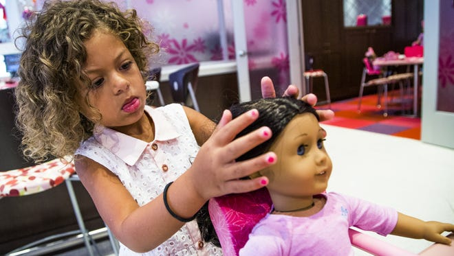 """Jaelyn Kangas, 4, of Scottsdale, fixes the hair of her American Girl doll, """"Charlotte"""" while relaxing with her aunt in the Bistro inside the American Girl Doll store in Scottsdale on Aug. 19."""