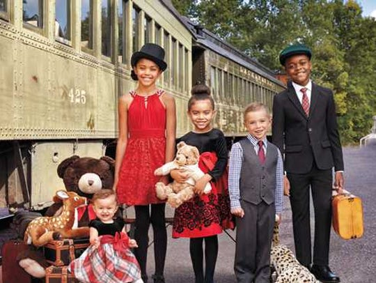 Kids are wearing nice clothes in front of a train