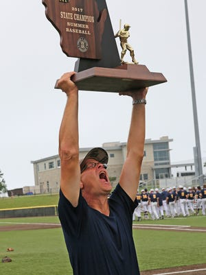 West Bend West coach Bill Albrecht yells to the crowd as he accepts the 2017 state championship trophy.