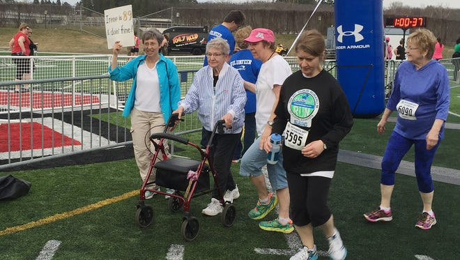 89-year-old Irene Pundsack of St. Cloud finishes FridayÕs Earth Day 5K surrounded by family members.
