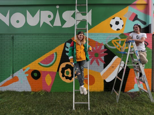 Jesse Kassel, 29, and Ellen Rutt, 26, both of Detroit  in front of their on their Nourish mural near shed 6 at the Detroit Eastern Market. This is the first Mural as a tease to the Murals in the Market festival that will bring 45 local and international artists to create new street murals around the Eastern Market in Detroit  on Friday, July 1, 2016.Jessica J. Trevino