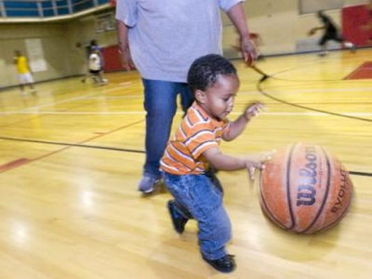 Najeeb Junior Moore, 2, gets his hands on a ball in this 2009 photo from a YMCA program during which the gym was opened on Saturday nights to give teens a place to hang out.