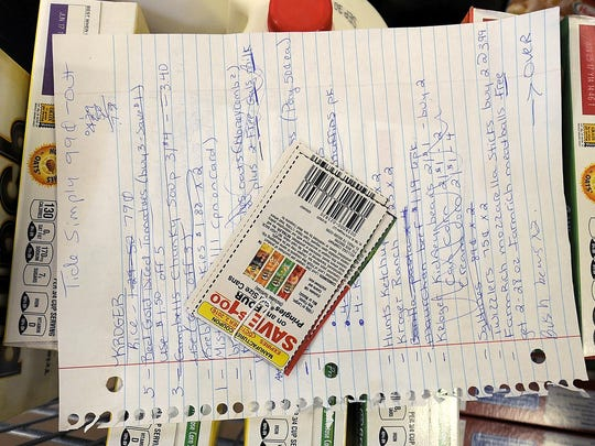 Coupons rest on top of Annette Spain's shopping list at the Kroger on University Parkway.