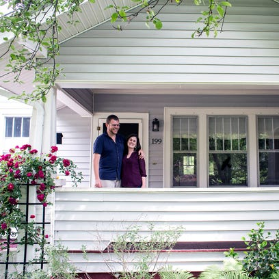 Jon Clancy, left, and fiancee Susanna Smith stand on the porch of their future North Asheville home on Edgewood Road. The couple have had a roller coaster ride of searching, offering, contracting and losing houses in the city.