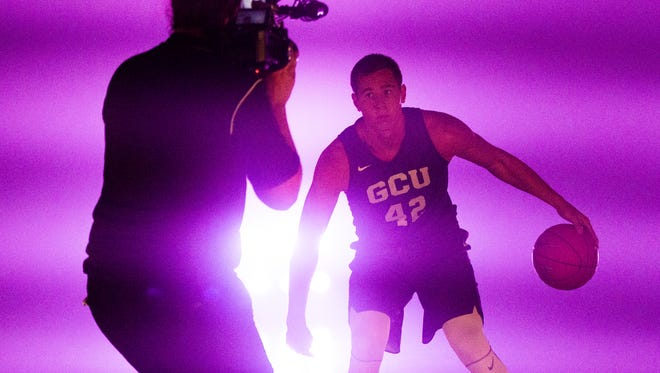 Grand Canyon University men's basketball player Gerard Martin strikes poses for a videographer in a smoke-filled gym at the school, Wednesday, September 6, 2017, as part of media day.