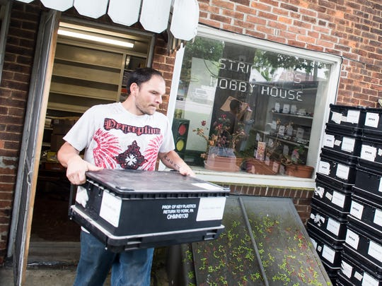 Stan Wolf Jr. of Thomasville Country Auction carries out a box of merchandise from Strickler's Hobby House in Hanover on May 10, 2018.