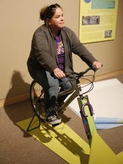 """Collections Manager Lizz Ricci pedals an electricity-generating stationary bicycle, part of the """"Green Revolution"""" exhibition opening today at the Farming Museum at Gateway Park."""
