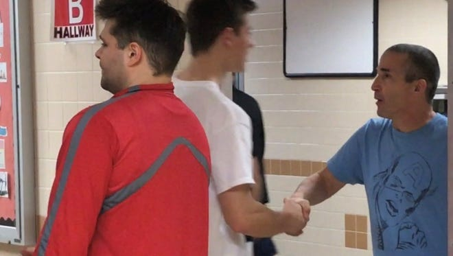 Penfield volleyball coach Mike Fusare, right, shakes the hand of player Danny Marcy, and assistant coach Nick Mickol, left, does the same with other players after one of the final practices of the season last month. It's a daily gesture for each player with each coach after every practice and game.