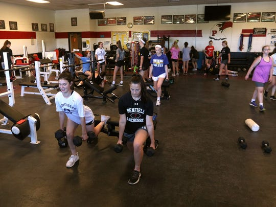 Senior lacrosse players Shannon Burdick, left, and Morgan Cox, work out at Penfield High School. Many area athletes take advantage of summer weight-training programs offered by their schools.