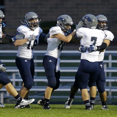 Xavier football players celebrate during their Bay