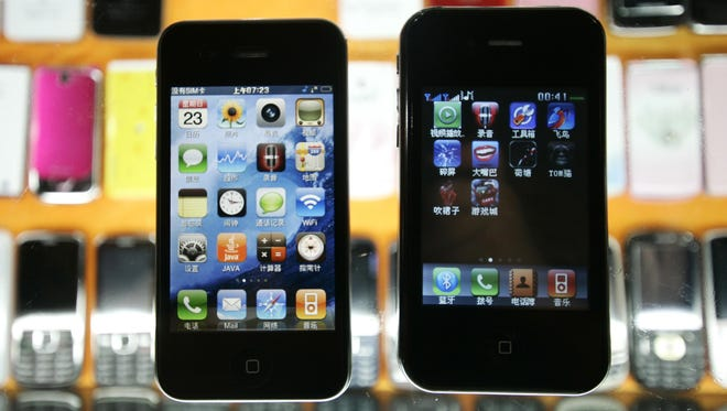 Two different fake iPhones are shown at a mobile phone market Sunday, Aug. 14 in Shanghai, China. (AP Photo)