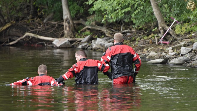 The Sheriff's Office dive team members join arms while conducting a search for 6-year-old Hamza Elmi on Friday near the location where his scooter was found on the banks of the Mississippi river in St. Cloud. Elmi went missing from his home nearby at about 8:40 p.m. Thursday. His body was recovered in the river Friday.