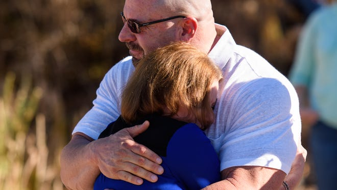 Iris Ross' brother Will Justin Smith and half-sister Laura Sutherland comfort each other at the memorial for Ross and her children, Nigel and Anora, on Dec. 30, 2017. Ross and the children were slain Dec. 25.