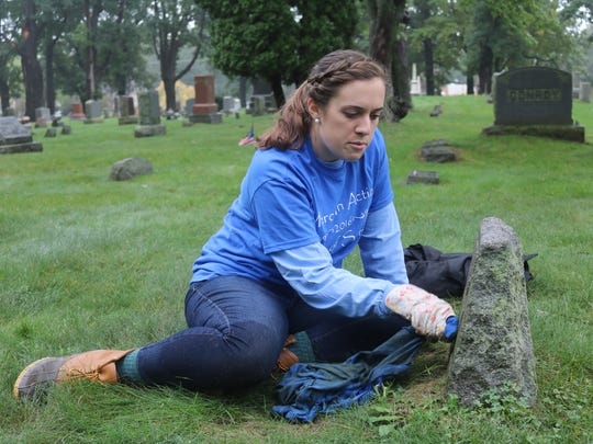 Erin Somerville tends to an aged headstone in Oakland Cemetery.