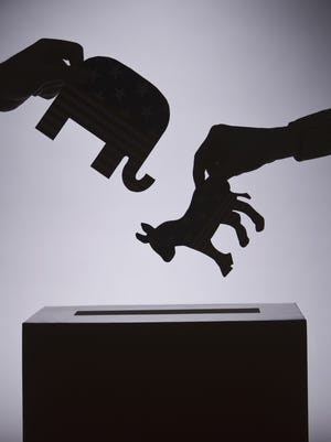 People are shown putting political symbols in a ballot box.