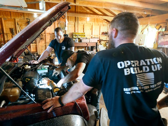 File photo: From left, Marines Alec Andrest and Justin Cogswell, and Army veteran Dave Rogers, all with Operation Build Up, work on a car that the group donated to a struggling veteran in 2017.