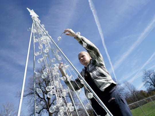 Anna Ball, 11, attaches lights to a Christmas tree