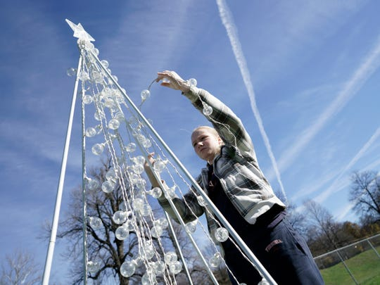 Anna Ball, 11, attaches lights to a Christmas tree at Gypsy Hill Park in honor of the military on Saturday, Nov. 21, 2015. The collection of trees was organized by the Wilson Middle School chapter of Family Career and Community Leaders of America.