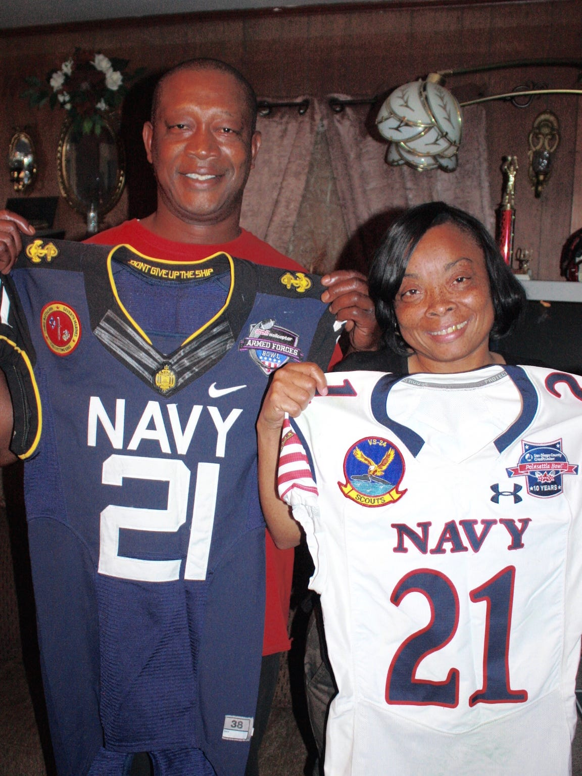 DeBrandon Sanders' dad and mom, Steven Harris and Carrie Sanders Harris of Itta Bena, hold the jerseys worn by their son in Navy's bowl victories the past two seasons. Navy won the Armed Forces Bowl in Fort Worth in 2013 (blue jersey) and the 2014 Poinsettia Bowl in San Diego.