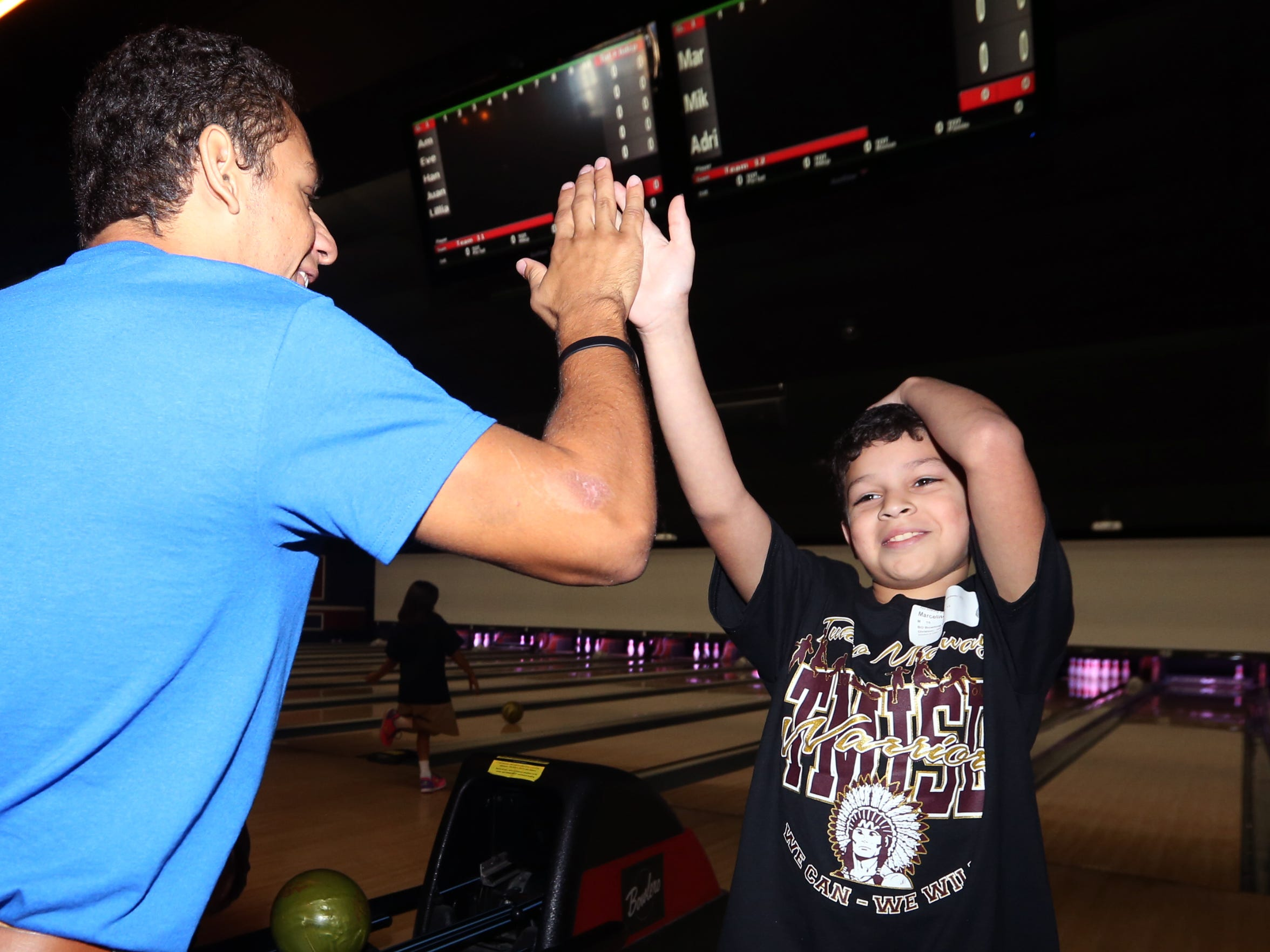 Volunteer Andres Lankenau gives athlete Marcelito Davila, 10, a high five after he earned a strike while he competes in the Special Olympics bowling tournament at Bowlero on Friday, November 4, 2016.