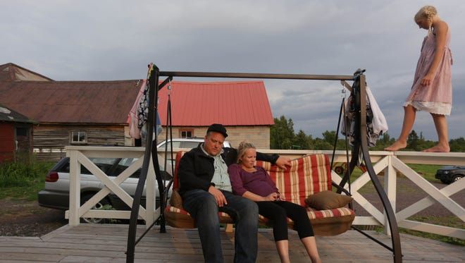 Mark and Riikka Hepokoski share a porch swing as their daughter Greta walks along the railing. The couple is teaching their kids Finnish folk dancing, the Finnish language and little ways of the culture.