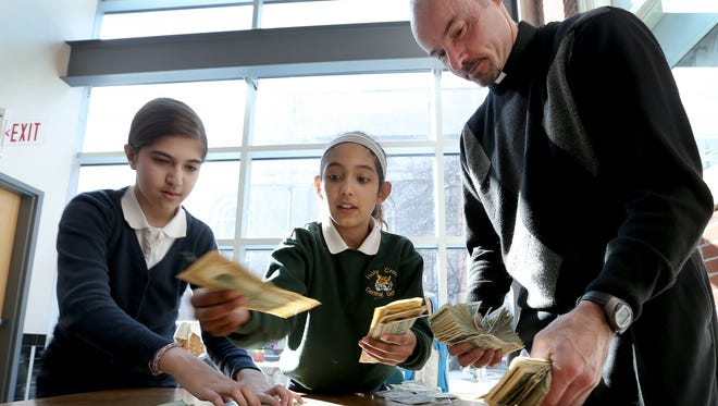 From left, Myleba Antunes, Melissa Gamero and Pastor Chris Wadelton the money donated by students at Holy Cross Central School in Indianapolis.