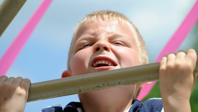 Lepardo, 7, of Ruckersville fights to get his chin above the bar as he participates in a competition to see who can do the most pull-ups during XtremeFest of the Blue Ridge held at Ridgeview Park in Waynesboro on Saturday, May 15, 2010.